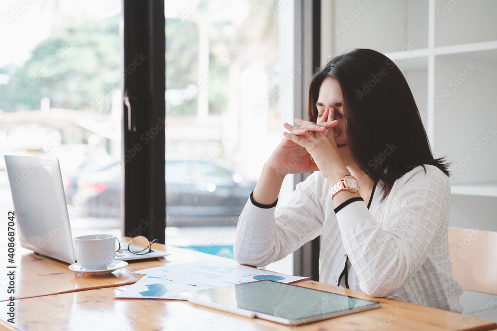Fototapeta Tired frustrated young asian businesswoman feeling stressed holding head with hands, business problem failure concept