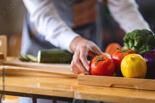 Fototapeta A female chef holding and picking a fresh tomato from a vegetables tray on the t