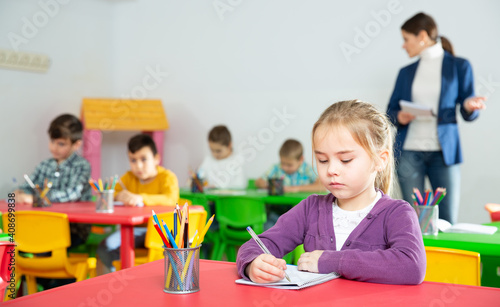 Obraz Portrait of assiduous little girl with pen and notebook at lesson in elementary school - fototapety do salonu