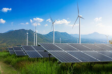 Photovoltaic Modules Solar Power Plant With Wind Turbines Against Mountains Landscape Against Blue Sky With Clouds,Alternative Energy Concept,Clean Energy,Green Energy.