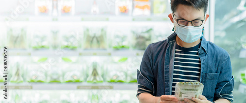 Obraz asian male wears medical mask against coronavirus while grocery shopping in supermarket or store- health, safety and pandemic, makes shopping during quarantine time - fototapety do salonu
