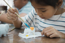 Close Up Asian Child Girl Is Concentrating To Paint On Small Ceramic Elephant With Oil Color. Kids Arts And Crafts Creative Activity Class In School.