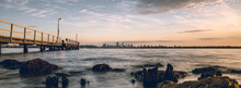 Beautiful Shot Of The Sea Coast And The Wooden Dock Overlooking A Cityscape