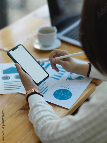Obraz Businesswoman using smartphone while analysing business chart in office room - fototapety do salonu