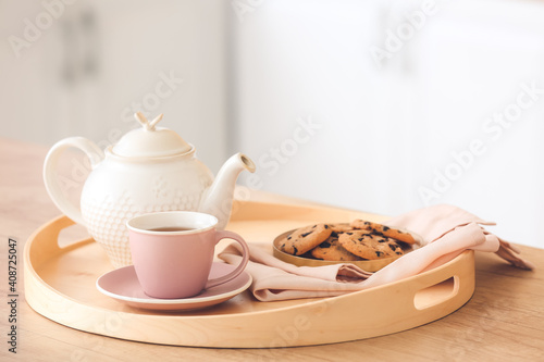 Tray with teapot, cup and cookies on kitchen table © Pixel-Shot