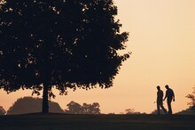 Silhouette Of Two Male Golfers On Golf Course At Sunrise
