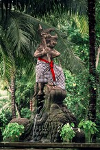Statue Of A Warrior Wearing A Checkered Skirt Conquering Lion In The Forest, Bali, Indonesia