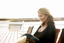 Ecuador, Galapagos Islands, Woman Reading Magazine While Sitting At Table On Deck Of Cruise Ship