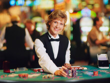 Female Casino Worker Placing Gambling Chips On A Table