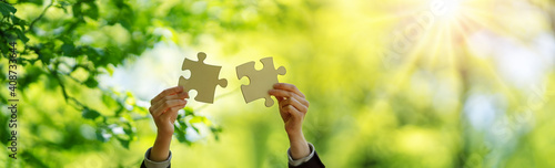 Human hand with piece of jigsaw outdoors on the nature background. © candy1812