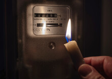 Power Outage, Blackout Concept.  A Man With Candle In Complete Darkness Looking On Electricity Meter At Home.