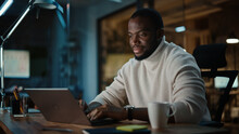 Handsome Black African American Man Having An Online Conversation On A Laptop Computer In Creative Office Environment. Happy Male Is Browsing Social Media And Replying To Friends In Messenger.
