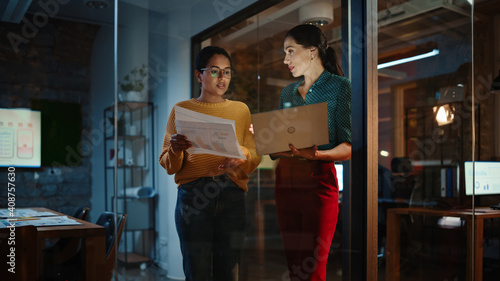 Fototapeta Two Diverse Multiethnic Women Have a Conversation in a Meeting Room Behind Glass Walls in an Agency. Creative Director and Project Manager Talk About Business Results and App Designs in an Office. obraz