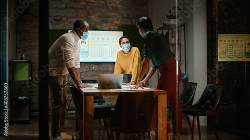 Obraz Diverse Multiethnic Team Wearing Face Masks During a Meeting Room Conversation Behind Glass Walls in Creative Office. Social Distancing Restrictions Concept in Work Place During Coronavirus Pandemic. - fototapety do salonu