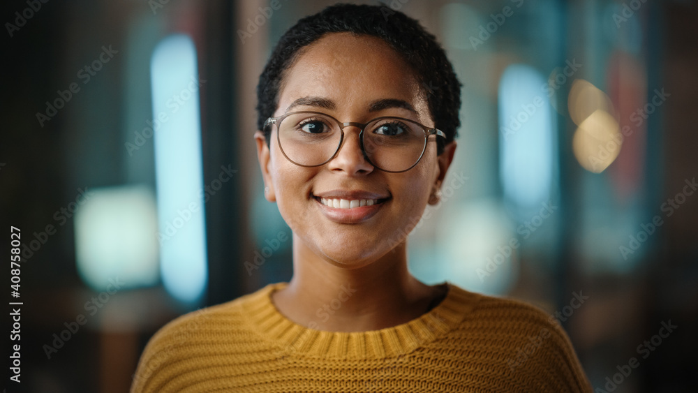 Fototapeta Close Up Portrait of a Young Latina with Short Dark Hair and Glasses Posing for Camera in Creative Office. Beautiful Diverse Multiethnic Hispanic Female Wearing Yellow Jumper is Happy and Smiling.