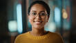 Close Up Portrait of a Young Latina with Short Dark Hair and Glasses Posing for Camera in Creative Office. Beautiful Diverse Multiethnic Hispanic Female Wearing Yellow Jumper is Happy and Smiling.