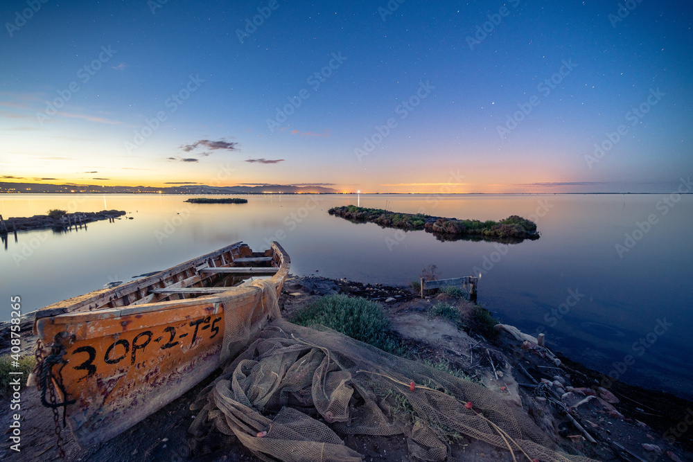 Fototapeta Old wooden fishing boat on the shore of a sea during sunset in Cambrils, Spain