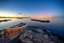 Old Wooden Fishing Boat On The Shore Of A Sea During Sunset In Cambrils, Spain