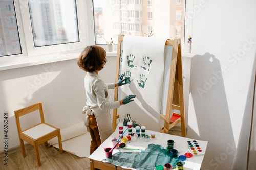 Canvas Print Child painting her hand with paint and paintbrush