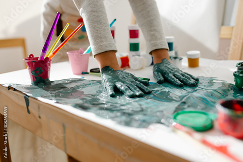 Slika na platnu Child painting her hand with paint and paintbrush