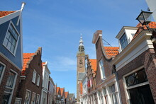 Colorful Facades Of Historic Houses In Edam, North Holland, Netherlands, With The Speeltoren (Carillon Tower) In The Background