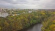 Aerial flight over a large overgrown autumn forest with views of city buildings. Kishinev, Moldova.