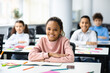 Portrait of small black girl sitting at desk in classroom