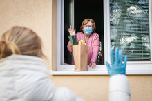 Social Distancing Due Coronavirus Covid-19 Pandemic Lockdown. Senior Woman With Face Mask Waving From Window To Her Adult Daughter She Delivered Groceries