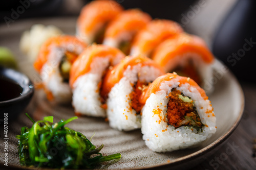 Fototapeta Sushi maki rolls with salmon, avocado, flying fish roe and cucumber on a plate with chopsticks, soy sauce, wasabi and ginger. Japanese traditional seafood served for lunch in modern gourmet restaurant obraz