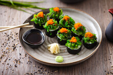 Sushi Maki Rolls With Crab, Seaweed Salad And Flying Fish Roe On A Plate With Chopsticks, Soy Sauce, Wasabi And Ginger. Japanese Traditional Seafood Served For Lunch In Modern Gourmet Restaurant