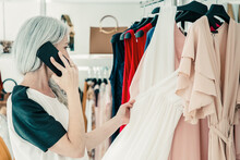 Fair Haired Woman Talking On Mobile Phone While Choosing Clothes And Browsing Dresses On Rack In Fashion Store. Medium Shot. Boutique Customer Or Retail Concept