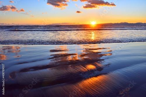 Fototapeta 干潮で波打ち際に映り込むオレンジ色の雲