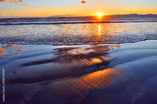 Obraz na plátně 干潮で波打ち際に映り込むオレンジ色の雲