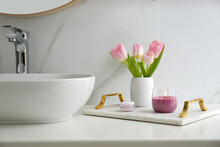 Beautiful Flowers And Candle On Countertop In Bathroom. Interior Decor