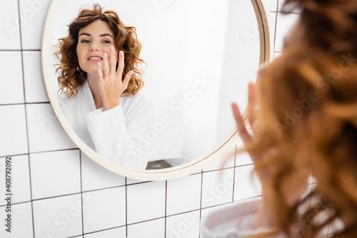 Obraz Smiling woman in bathrobe applying face cream near mirror on blurred foreground - fototapety do salonu