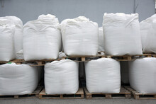 Large Bags Of Grain And Flour Are Stored In An Industrial Warehouse, Ready For Further Transportation And Processing.