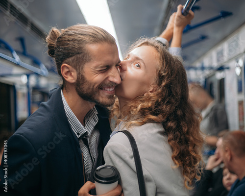Fototapeta happy couple standing in a subway train.