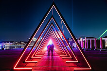 Light Tunnel Or Gate Of Light Installation Consists Of Many Triangular Gates Lit By Bright Lights. Blurred People Like An Aliens Invasion Cross A Deep Light Tunnel As Stars Are Visible In The Dark Sky