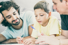 Two Fathers Helping Focused Boy With School Home Task, Lying On Floor At Home, Writing Or Drawing In Papers. Family And Gay Parents Concept