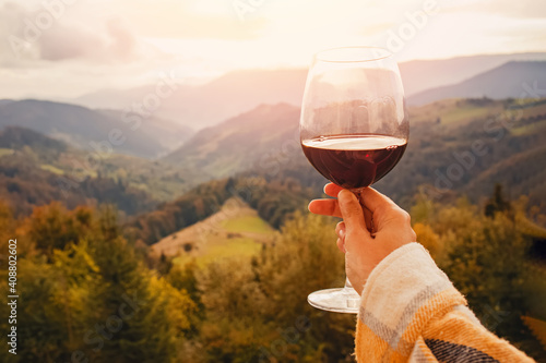 Fotografía Woman's hand holding a glass of red wine with a mountain view.