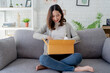 Asian women are very happy to sit on the sofa. She was carrying a small cardboard box in her lap. Customer is satisfied with the products ordered on the Internet.