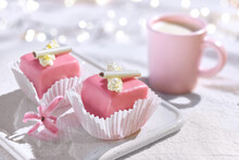Valentine Petit Fours With Marzipan Icing And Cream Flowers. Espresso Coffee In Pink Cup. Happy Valentine's Day Garland Of Lights On Ivory, Off White Textile Tablecloth. Pink Hyacinth Flower.