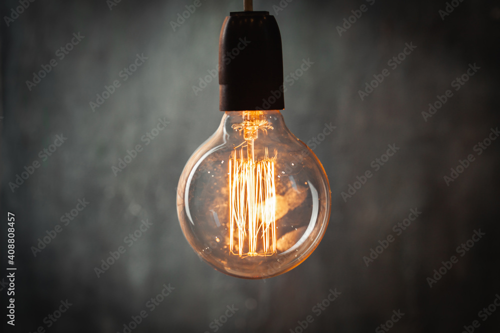Fototapeta incandescent light bulb with tungsten filaments on old rustic grey concrete wall background. Save the energy