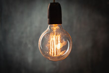Incandescent Light Bulb With Tungsten Filaments On Old Rustic Grey Concrete Wall Background. Save The Energy