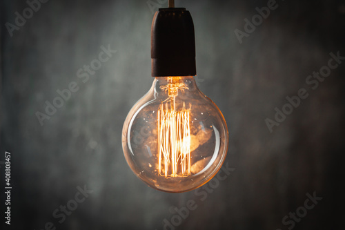 Obraz incandescent light bulb with tungsten filaments on old rustic grey concrete wall background. Save the energy - fototapety do salonu