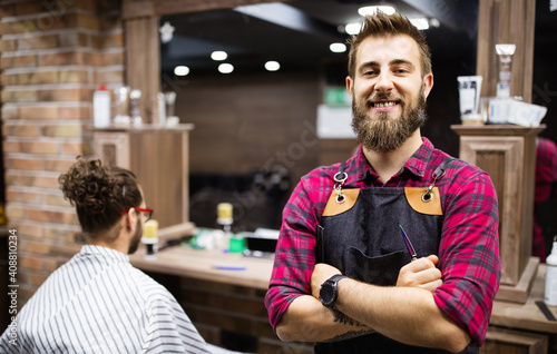 Cuadros en Lienzo Barber man in an apron with arms crossed and happy in salon