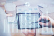Double exposure of man's hands holding and using a phone and financial chart drawing. Market analysis concept.