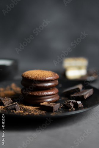 Foto Round chocolate brownie on a black plate and cocoa powder on a gray concrete table