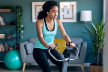 Sporty African Young Woman Exercising On Smart Stationary Bike And Listening To Music At Home.