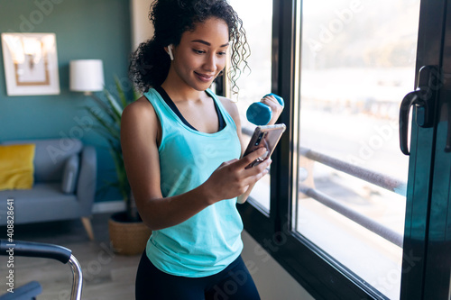 Obraz Beautiful gymnast woman doing muscular exercise with dumbbells while using smart phone in living room at home. - fototapety do salonu